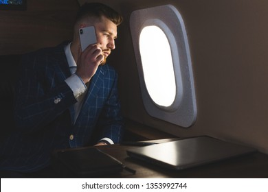 Young attractive and successful businessman talking on the phone and working while sitting in the chair of his private business plane