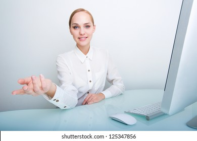 Young attractive successful businesswoman looking at the camera inviting or showing something