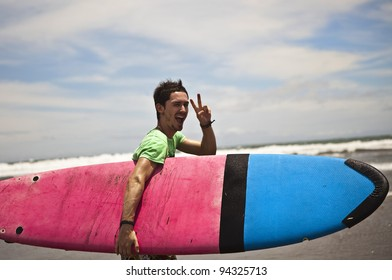 Young attractive surfer with a surf board