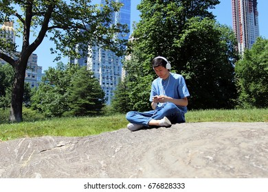 Young attractive technological man sitting in urban city park using smartphone and listening to music on white headphones