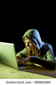young attractive teen woman wearing hood on looking dark and dangerous hacking laptop computer system on black background in cybercrime or cyber crime and internet criminal concept
