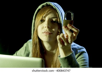young attractive teen woman wearing hood on looking dark and dangerous hacking laptop computer system holding lock in cybercrime or cyber crime and internet criminal concept