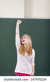 Young attractive young teenage girl student rejoicing by cheering and raising her arm in the air in front of the blackboard in the classroom