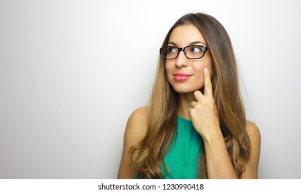 Young attractive thinking woman looking to the side with finger on cheek and glasses over white background. Copy space.