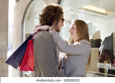 Young attractive tourist couple hugging outside a store window  with paper shopping bags, while on vacation, smiling.