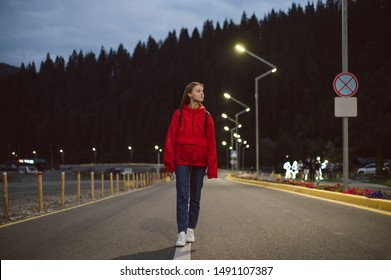 Young attractive tourist girl walking alone down the moutain highway in the evening. Female traveler in a red raincoat strolling near the mountain coniferous forest. Mountain woods on the background.