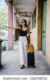 A young, attractive and urbane Indian woman socialite hails a cab as she stands next to her baggage suitcase and bag in a walkway in the city. She is elegantly dressed in casual clothes and sunglasses