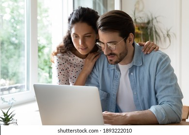 Young attractive wife hugging husband wearing glasses from back, looking at laptop screen together, using computer, spouses surfing internet, shopping online, making purchases, booking tickets