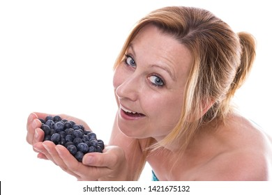 Young attractive woman with 2 hands full of blueberries looking into the camera