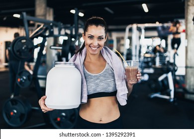 Young attractive woman after successful workout posing and smiling in modern fitness gym while holding big white protein jar and glass of shake with drinking straw in other hand.