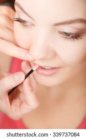 Young attractive woman applying lipstick on lips. Pretty gorgeous girl beautifying. Make up.