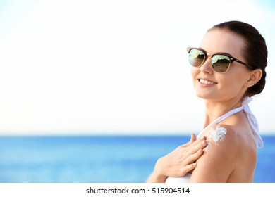 Young attractive woman applying sun protective lotion on shoulder