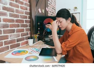 young attractive woman artist feeling tired and getting headache painful taking off glasses resting when she working long time in office.