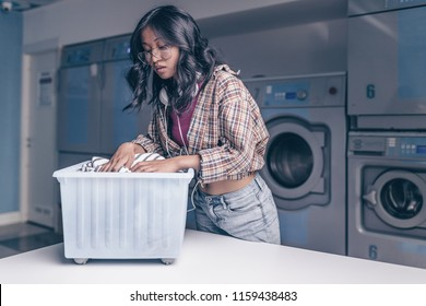 Young attractive woman with a basket in laundry