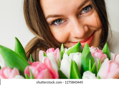 Young attractive woman with big eyes with flowers near her face. Sunny spring morning.
