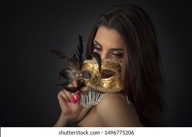 Young attractive woman in a black dress with golden carnival mask.