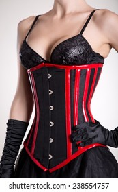 Young attractive woman in black and red corset, studio shot on white background
