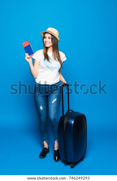 Young attractive woman in blue jeans and a hat with a suitcase isolated on blue background.
