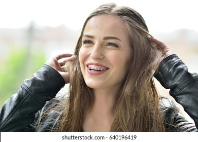 Young attractive woman with bracket system posing rainy spring outdoor and happy smiling. Malocclusion, brace, bracket, dental care, orthodontic health concept.