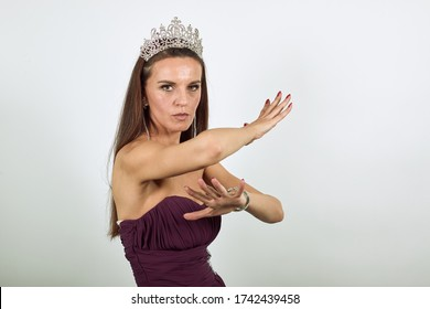 Young Attractive Woman Brunette In Purple Stylish Dress, With Crown On Head White Background, Aggressive Female Made Defensive Stance Hands And Is Ready To Strike. Human Self-Defense, Karate, Kung Fu