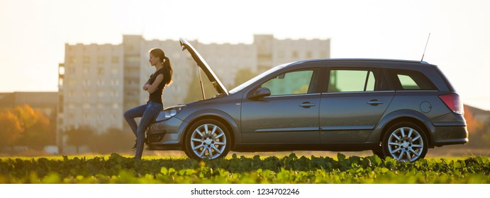 Young attractive woman at car with open hood in green meadow on blurred apartment building and clear bright sky copy space background. Transportation, vehicles problems and breakdowns concept.