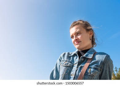 Young attractive woman in casual wear with hair tousled by the wind on a bright sunny day, blue sky in the background, copy space