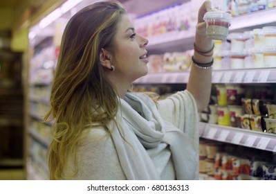Young attractive woman choosing food in a supermarket