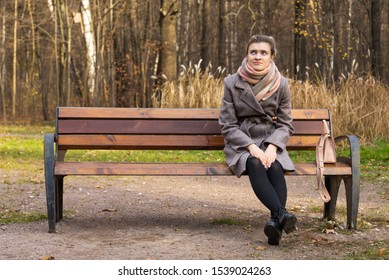 Young attractive woman in a coat and a long shawl sits on a bench in the autumn park