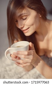 young attractive woman with a cup of tea in her hands looks away and smiles