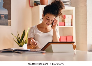 Young attractive woman with dark curly hair sitting at the table with notebook and tablet thoughtfully talking on cellphone studying at modern cozy home