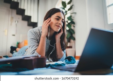 Young attractive woman digital designer working remotely at home lying having video call in modern living room using portable computer device, female student listening to music and chatting