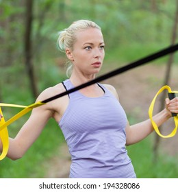 Young attractive woman does suspension training with fitness straps outdoors in the nature.