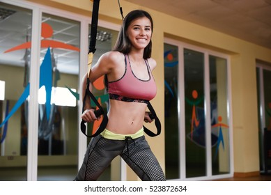 Young attractive woman does suspension training with fitness straps in the gym's studio