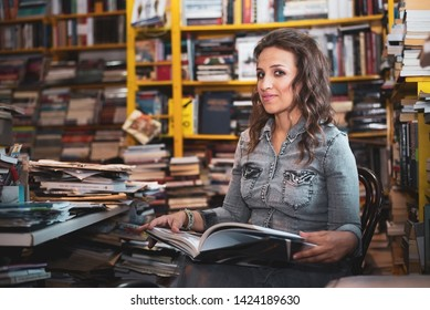 Young attractive woman doing research in the messy library, having a book open on her lap. Looking at camera.