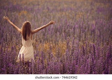Young attractive woman in dress at flower field.