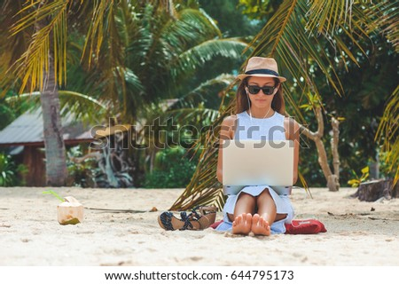 Young attractive woman in dress, sunglasses and hat, working in laptop on the beach, on palm trees background, Girl Freelancer working