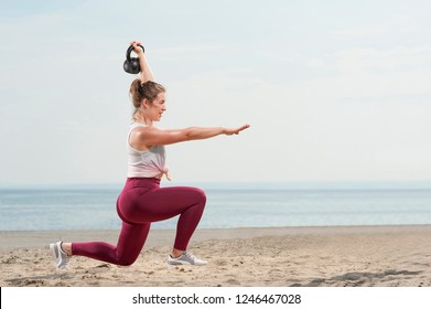 Young attractive woman dressed in pink leggings doing a squat with a kettle bell by the seaside. Fitness woman working out at the beach. Fitness Concept.