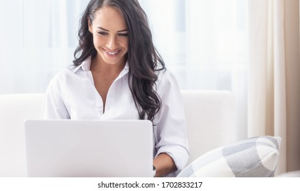 Young attractive woman dressed in white shirt working from home on a notebook in her living room, smiling.