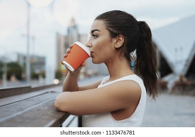 Young attractive woman drinking coffee from red cup.