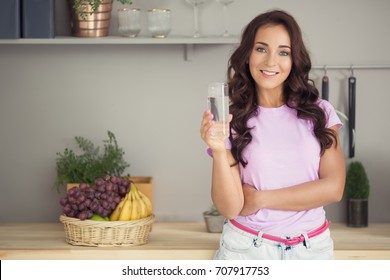 Young attractive woman drinking water on kitchen.
