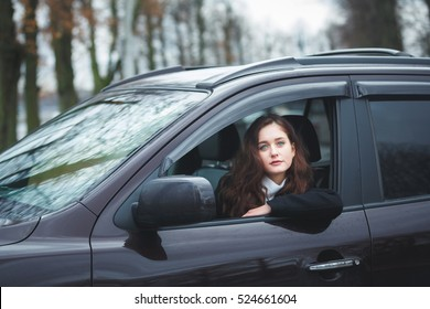 Young attractive woman driving the car in rain