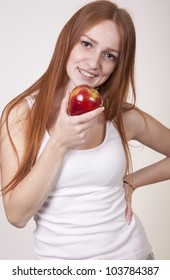 Young attractive woman eating a red apple.