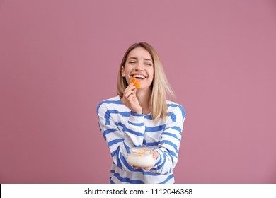 Young attractive woman eating tasty yogurt on color background