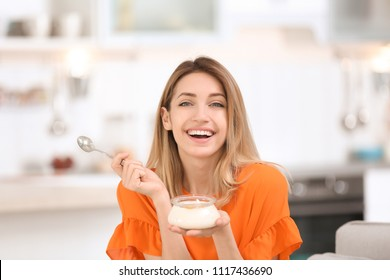 Young attractive woman eating tasty yogurt in kitchen