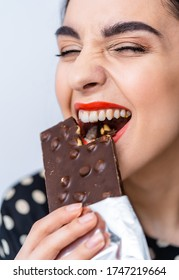 Young attractive woman eats chocolate. Close up. Black chocolate with nuts. Beautiful woman eats chocolate with nuts. Red lips. Nice smile.