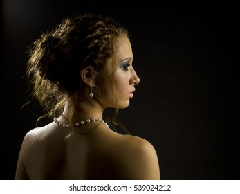 Young attractive woman with an elegant open shoulder look portrait shot in studio against a black background