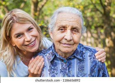 Young attractive woman embracing old grandmother outdoor. Female - generations - love