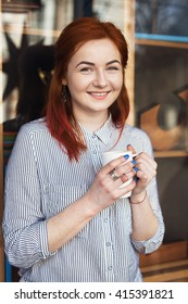 Young Attractive Woman Enjoying A Cup Of Coffee in Cafe