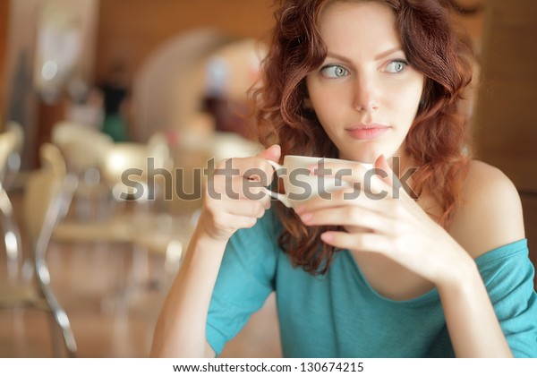Young Attractive Woman Enjoying A Cup Of Coffee in Cafe. redheaded lady holds cup of coffee in her hands while looking away. Copyspace
