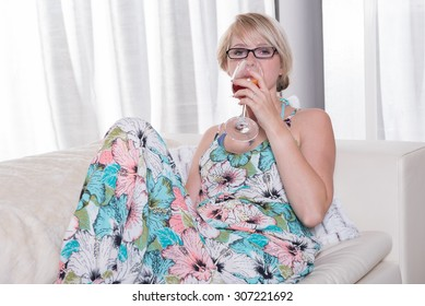 young attractive woman enjoys a cocktail on the couch
